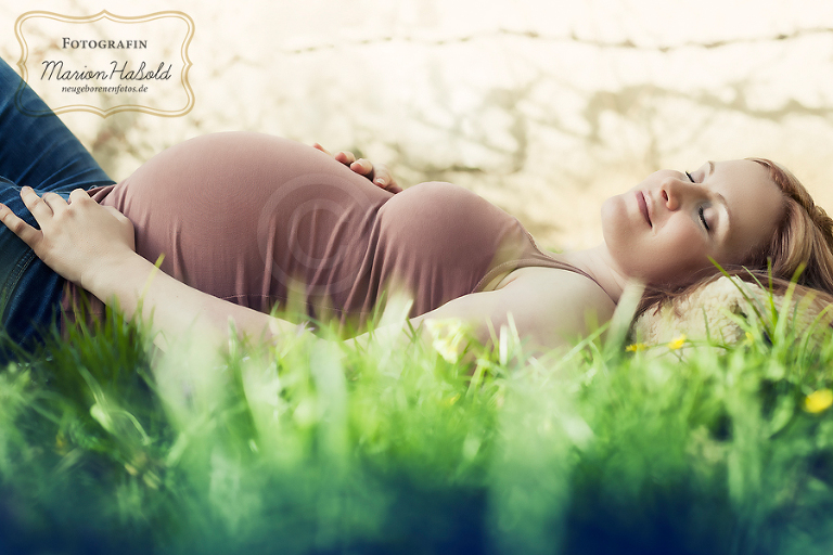 Babbauchfoto einer liegenden Schwangeren im Grünen im Raum Esslingen